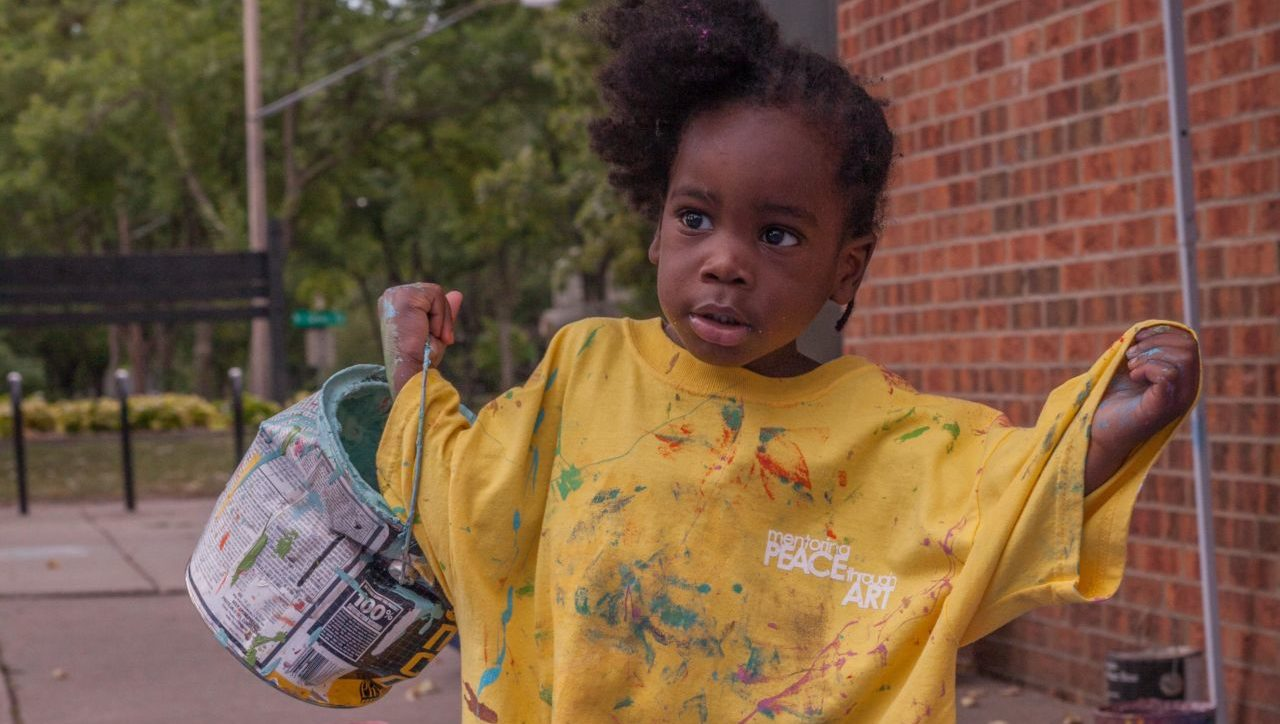 Girl in yellow shirt carrying paint can