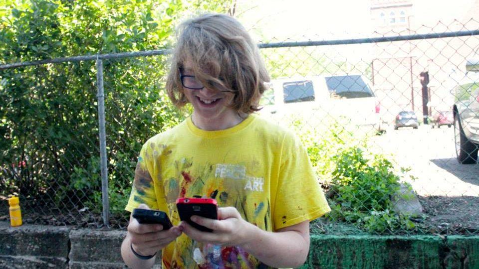 Teenager wearing yellow shirt using two smartphones