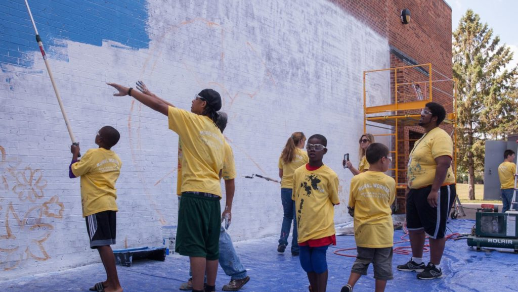 Group of young people in yellow shirts working on mural